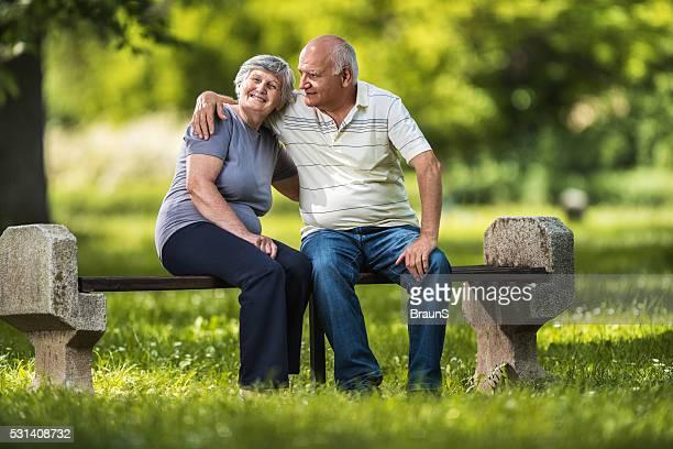 Selbstverständlich Seniorenpaar entspannenden auf einer Bank im park.