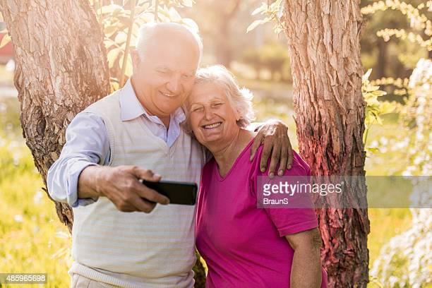 Selbstverständlich altes Paar nehmen selfie mit Handy im Freien