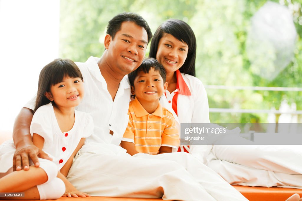 Embraced Thai family sitting on sofa in living room. : Stock Photo