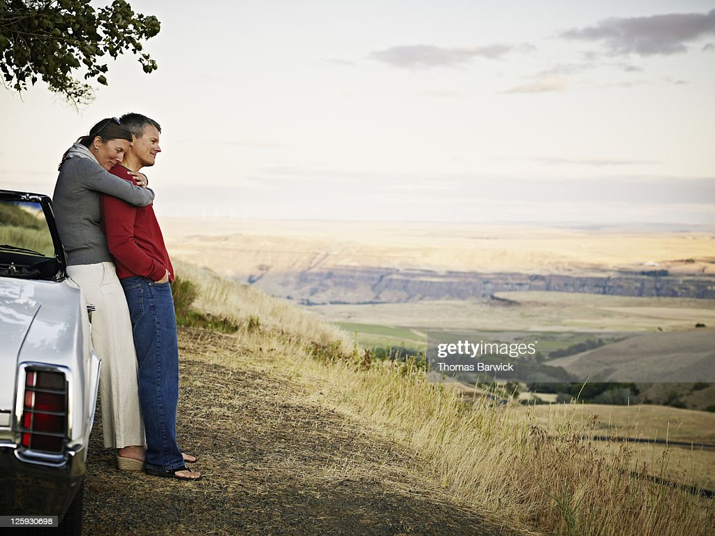 Embracing couple leaning against convertible : Stock Photo