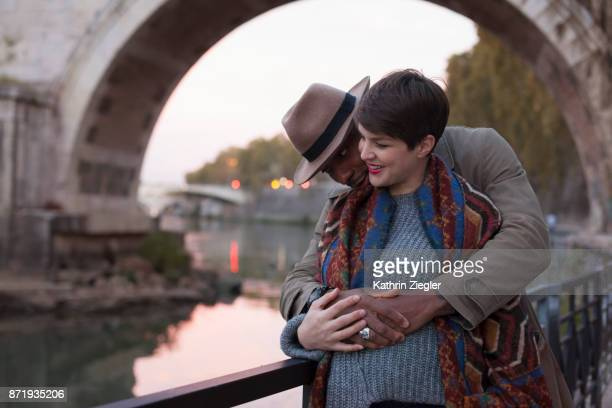 Embracing pregnant couple at Tiber River, Rome, Italy