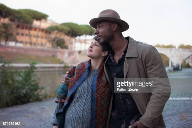Embracing pregnant couple walking along Tiber River, Rome, Italy