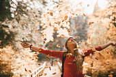 Playful young hiker throwing autumn leaves in the air in the colorful forest and embracing the nature