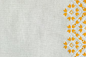 Embroidered fragment on flax by yellow and white cotton threads. Macro embroidery texture flat stitch. Geometric ornament.