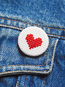 Embroidered heart button badge on denim jacket