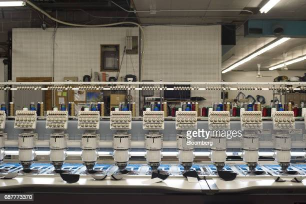 Embroidery machines stitch designs onto baseball hats at the Graffiti Caps production facility in Cleveland Ohio US on Tuesday May 9 2017 The US...