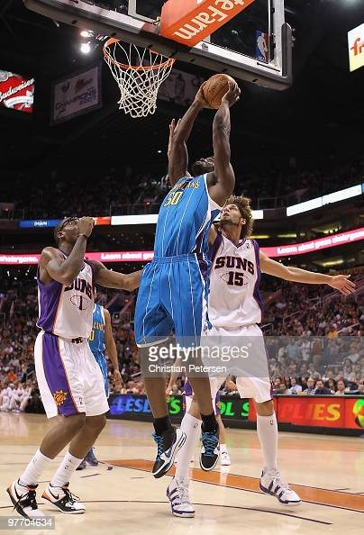 Emeka Okafor of the New Orleans Hornets puts up a shot over Amar'e Stoudemire and Robin Lopez of the Phoenix Suns during the NBA game at US Airways...