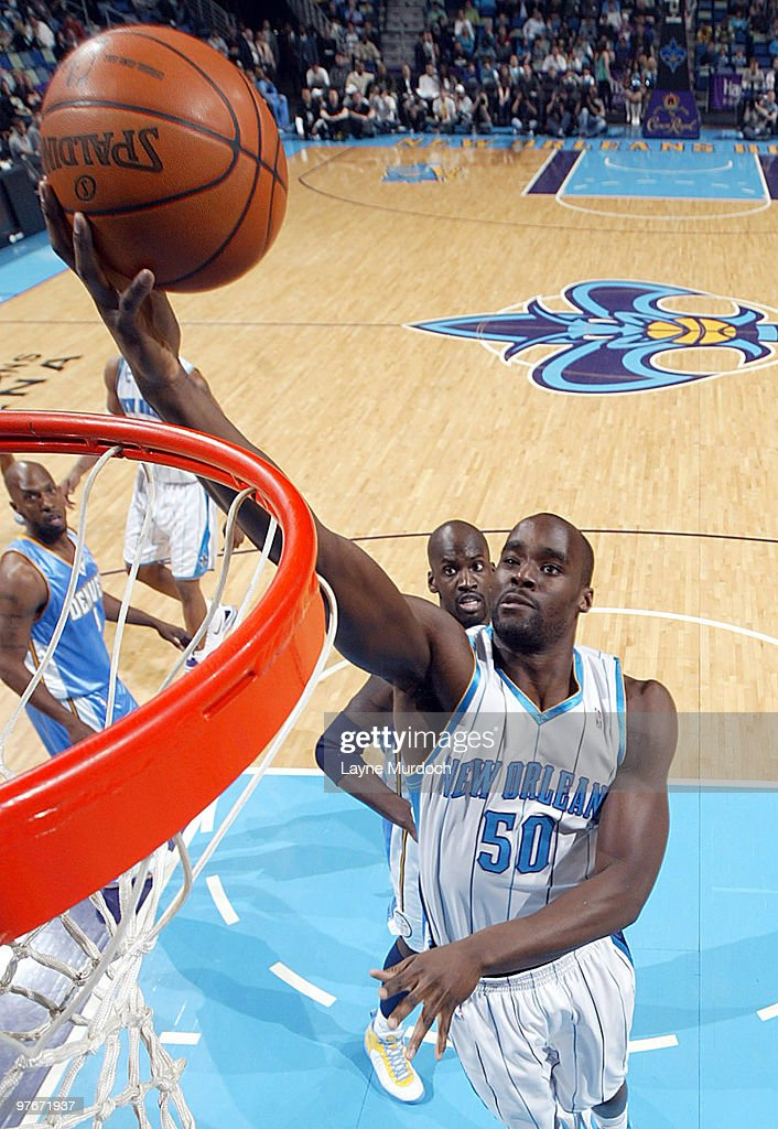 Emeka Okafor of the New Orleans Hornets shoots over Chauncey Billups and Johan Petro of the Denver Nuggets on March 12 2010 at the New Orleans Arena...