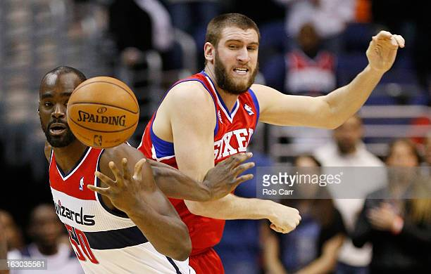 Emeka Okafor of the Washington Wizards steals the ball from Spencer Hawes of the Philadelphia 76ers during the first half at Verizon Center on March...