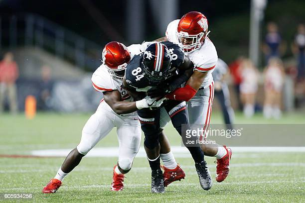 Emeke Egbule and Brandon Wilson of the Houston Cougars make a tackle against Nate Cole of the Cincinnati Bearcats in the first half at Nippert...