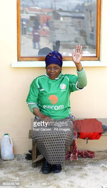 Emeli Ntsitshe wearing a Donecarney Celtic football shirt celebrates after receiving the keys to her first home in Wallacdene Township in Capetown...