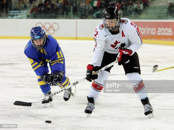 Emelie O Konor of Sweden fights for the puck with Hayley Wickenheiser of Canada during the women's ice hockey Preliminary Round Group A match between...