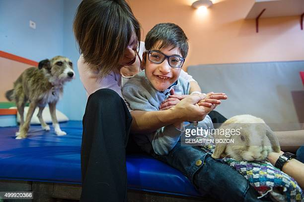 Emeline Chancel a therapist specialized in animalassisted therapy works with Zinedine a child with multiple disabilities during a session of...