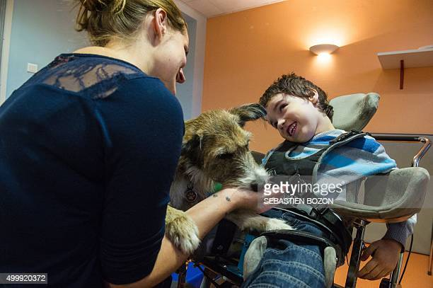 Emeline Chancel a therapist specialized in animalassisted therapy works with Nathan a child with multiple disabilities during a session of meditation...