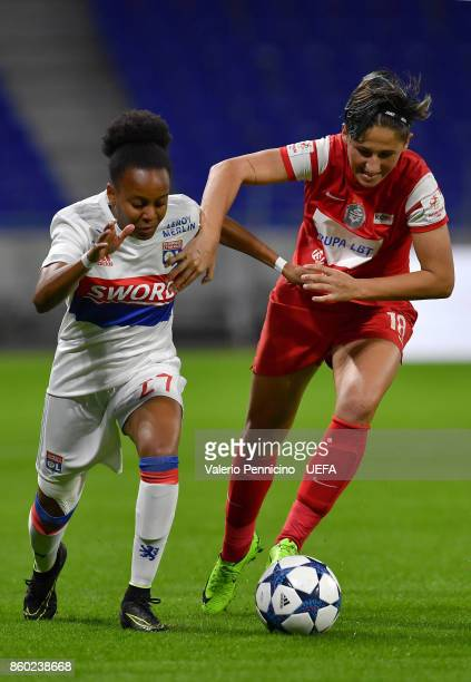Emelyne Laurent of Lyon is challenged by Maria Ficzay of Medyk Konin during the UEFA Women's Champions League Round of 32 Second Leg match between...