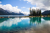 The clear, tranquil waters of Garibaldi Lake in Garibaldi Provincial Park near Whistler in British Columbia, produce bottle-green reflections of an island of conifers.  In the foreground close to shor