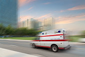 speeding ambulance on street in modern city ,emergency medical concept