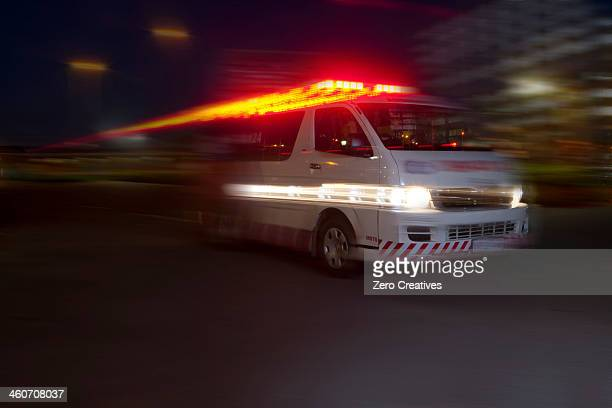 Emergency ambulance speeding through city at night