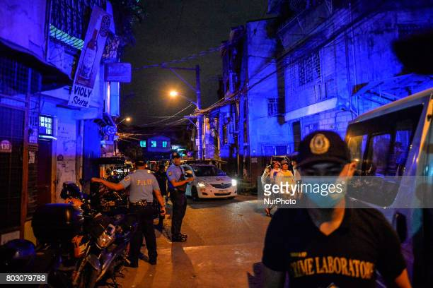 Emergency blinkers illuminate a street as police investigators arrive at the scene of a shooting victim in Marikina east of Manila Philippines...