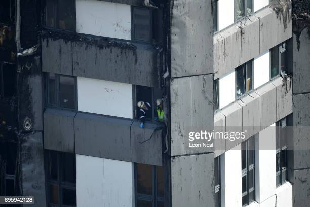 Emergency crews look out the window of the 24 storey residential Grenfell Tower block in Latimer Road West London on June 14 2017 in London England...