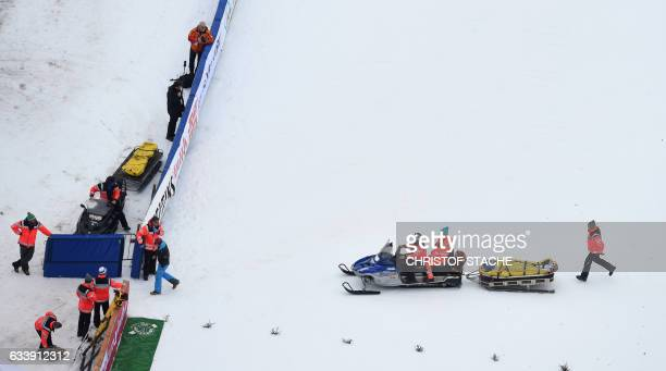 Emergency doctors transport Austria's ski jumper Gregor Schlierenzauer after a crash during his qualification jump for a second FIS ski jumping World...