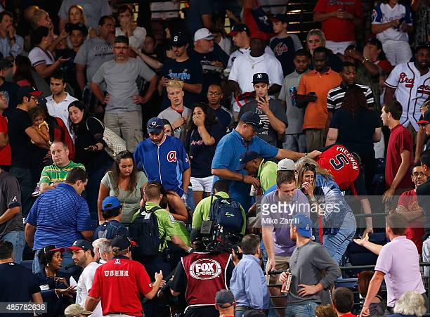 Emergency medical staff help a fan that fell from the upper deck of Turner Field during the game between the Atlanta Braves and the New York Yankees...