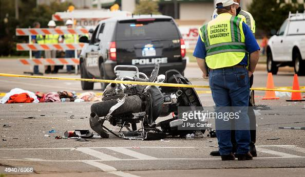 Emergency officials stand over a crash scene including a wrecked police motorcycle after a suspected drunk driver crashed into a crowd of spectators...