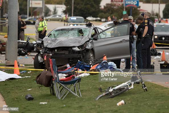 Emergency officials stand over the car that was involved after a suspected drunk driver crashed into a crowd of spectators during the Oklahoma State...