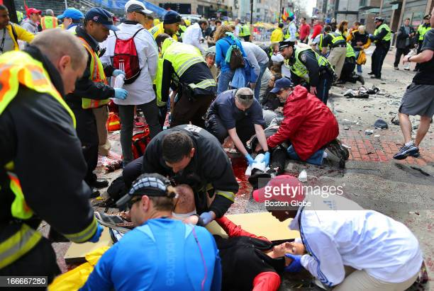 Emergency personnel aid the injured on the sidewalk at the scene of the first explosion near the finish line of the Boston Marathon