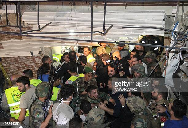 Emergency personnel and army soldiers gather at the site of a twin suicide bombing in Burj alBarajneh in the southern suburbs of the capital Beirut...