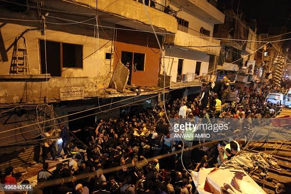 Emergency personnel and civilians gather at the site of a twin suicide bombing in Burj alBarajneh in the southern suburbs of the capital Beirut on...