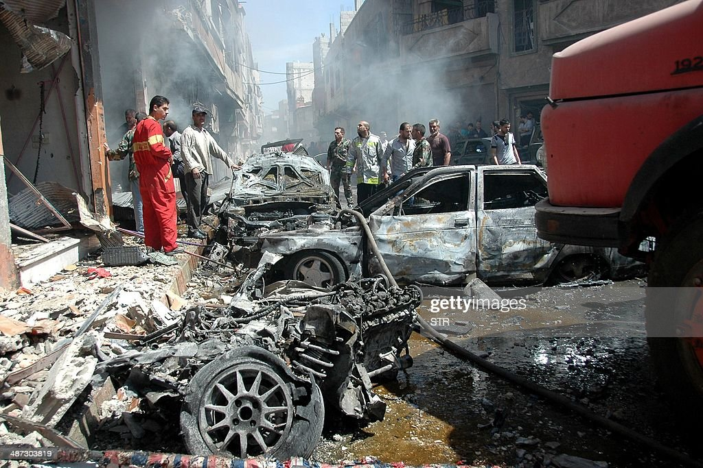 Emergency personnel and civilians inspect the site following a car bomb explosion in the Abbasiyah neighbourhood of Syria's central city of Homs on...