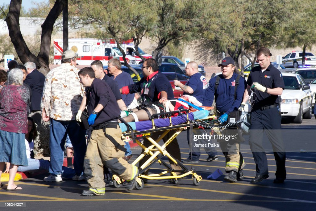 Emergency personnel and Daniel Hernandez (C), an intern for U.S. Rep. Gabrielle Giffords (D-AZ), move Giffords after she was shot in the head outside a shopping center January 8, 2011 in Tucson, Arizona. Hernandez helped to save Giffords' life after she was shot in the head. U.S. Rep. Gabrielle Giffords (D-AZ), and more than a dozen other people were injured and six people were killed at public event entitled Congress on your Corner when a gunman opened fire.
