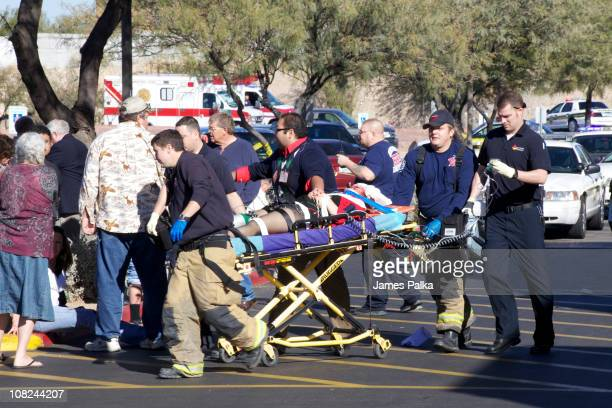 Emergency personnel and Daniel Hernandez an intern for US Rep Gabrielle Giffords move Giffords after she was shot in the head outside a shopping...