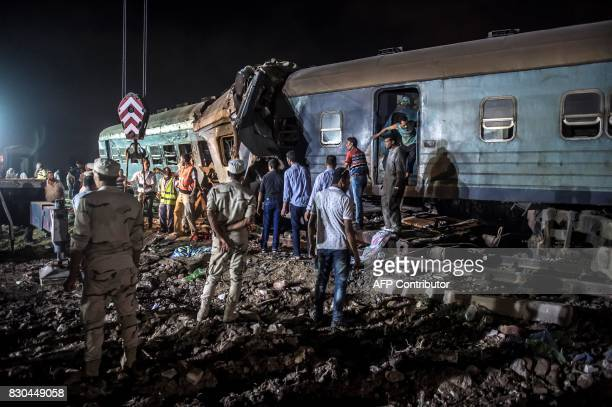 TOPSHOT Emergency personnel and Egyptian military police search the wreckage of the train collision on August 11 2017 near Khorshid station in...