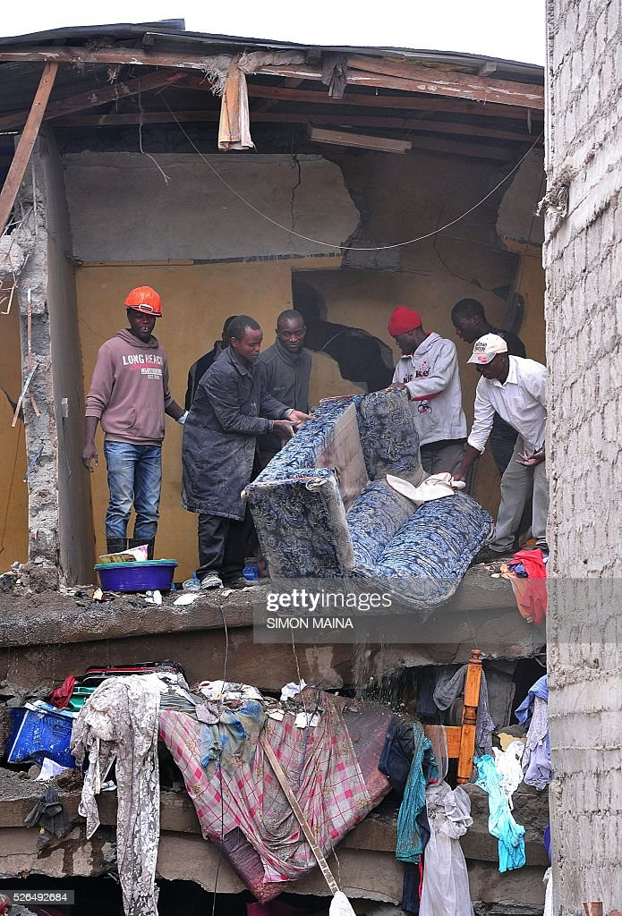 Emergency personnel clear debris after a building collapsed in Nairobi on April 30, 2016. Rescuers in the Kenyan capital made desperate efforts to free survivors including a woman and child trapped in a building that collapsed in storms that have left a total of 17 people dead. / AFP / SIMON
