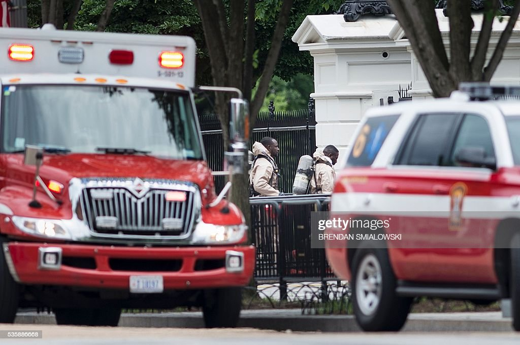 Emergency personnel in protective suits walk to the Northeast gate to the White House from Pennsylvania Avenue during a security lockdown of the White House grounds May 30, 2016 in Washington, DC. / AFP / Brendan Smialowski
