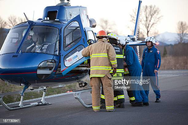 Emergency personnel load an accident victim into a helicopter.
