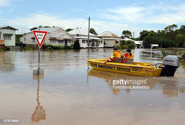 Emergency personnel look for residents in need of evacuation after the swollen Fitzroy River broke its banks and flooded the city of Rockhampton on...