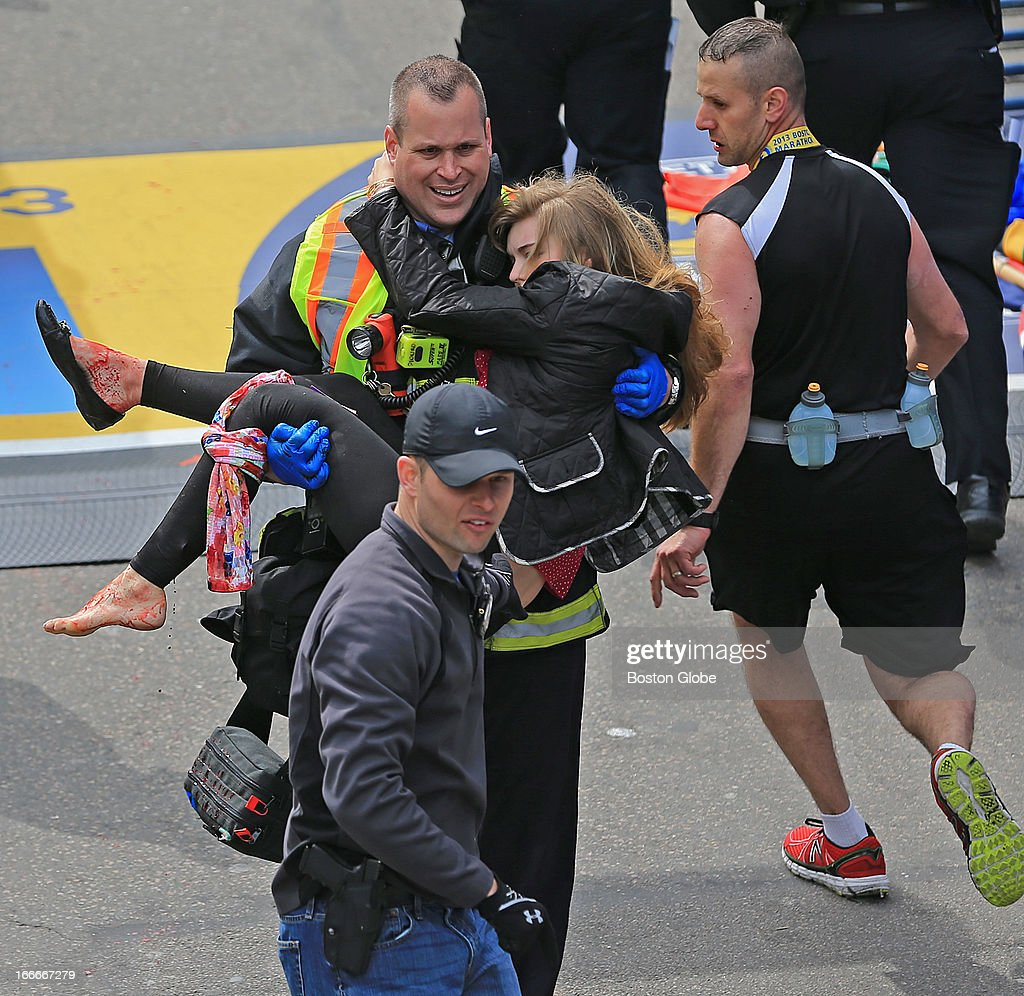 Emergency personnel respond to the scene after two explosions went off near the finish line of the 117th Boston Marathon on April 15, 2013. Victim Victoria McGrath is helped to a stretcher.