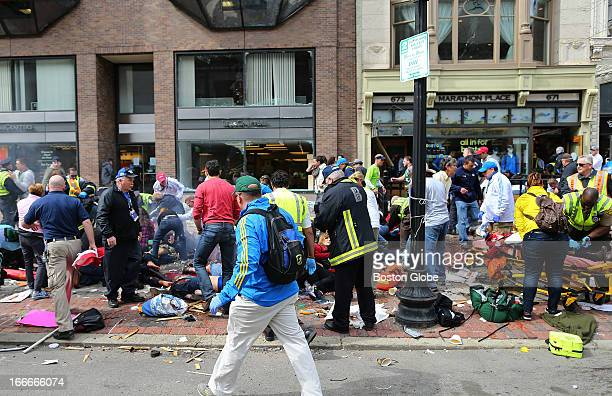 Emergency personnel respond to the scene of the first explosion on Boylston Street near the finish line of the 117th Boston Marathon April 15 2013