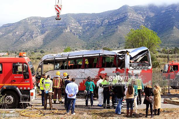 Emergency personnel stand before the righted bus on the Spanish AP7 motorway near Freginals Amposta south of Tarragona following a fatal accident...