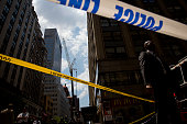 Emergency personnel stand on scene after a damaged crane hangs over Madison Avenue following an accident May 31 2015 in New York City At least ten...