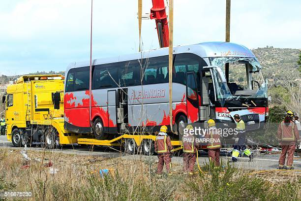 Emergency personnel standby as a crane loads a damaged bus onto a semitrailer on the Spanish AP7 motorway near Freginals Amposta south of Tarragona...