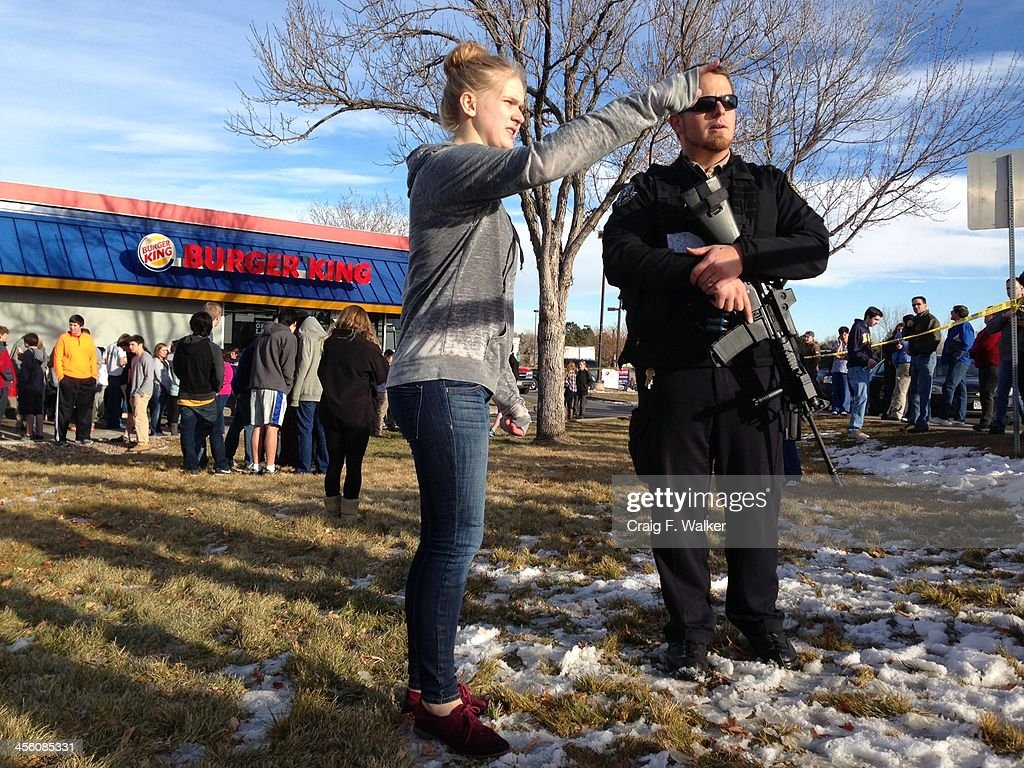 Emergency personnel, students and bystanders congregate outside a Burger King restaurant near Arapahoe High School in Centennial, Colo. after gun shots were reportedly fired inside the school on Friday afternoon, Dec. 13, 2013.