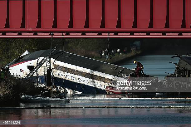 Emergency personnel work at an accident scene on November 15 2015 where a highspeed TGV train coach and engine carriage lie in a canal in Eckwersheim...