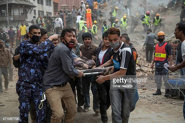 Emergency rescue workers carry a victim on a stretcher after Dharara tower collapsed on April 25 2015 in Kathmandu Nepal More than 100 people have...