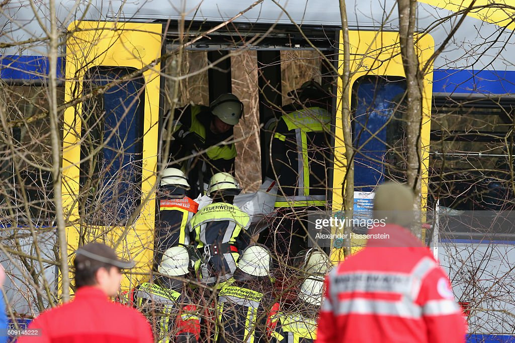 Emergency Rescue workers carrying a victim at the wreckage of two trains that collided headon several hours before in Bavaria on February 9 2016 near...