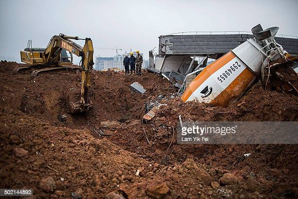 Emergency rescuers search a collapsed building after a landslide destroyed or damaged more than 30 buildings on December 21 2015 in Shenzhen China...