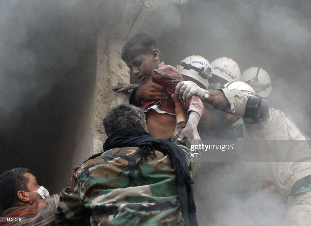 Emergency responders help evacuate a Syrian boy from a residential building reportedly hit by an explosives-filled barrel dropped by a government forces helicopter in the Shaar neighbourhood of the northern Syrian city of Aleppo on Arpil 6, 2014. More than 150,000 people have been killed in Syria's three-year war, with half the population estimated to have fled their homes.